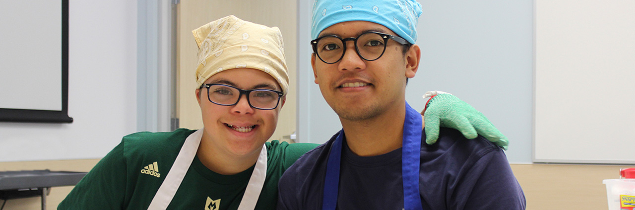 two youth wearing aprons, rubber gloves and headbands smiling and looking into the camera