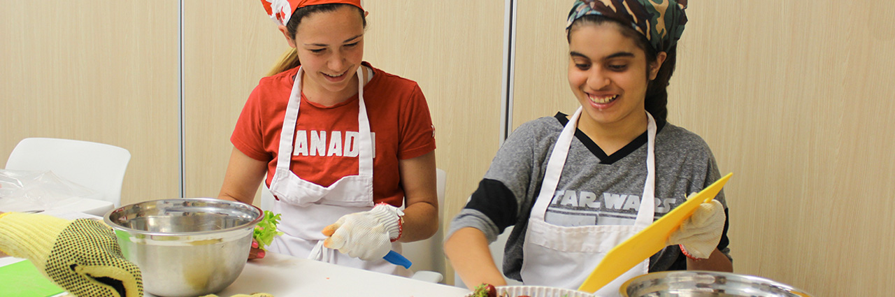 two adolescent women smiling and preparing food; they are wearing aprons, rubber gloves and headbands