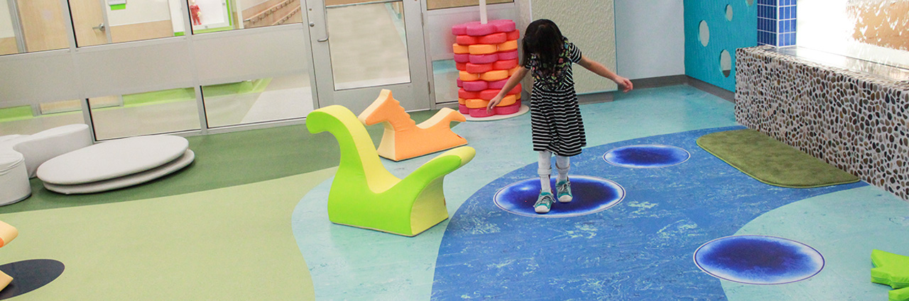 girl playing on coloured floor of RCC facility