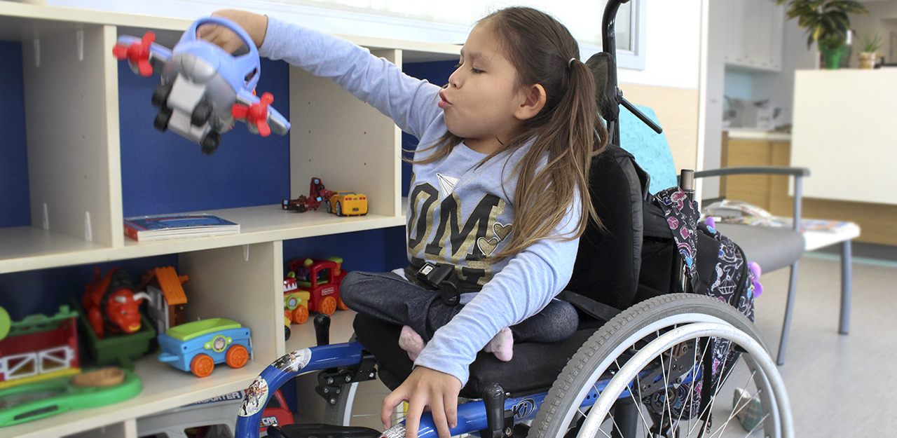 girl in wheelchair playing with toy plane